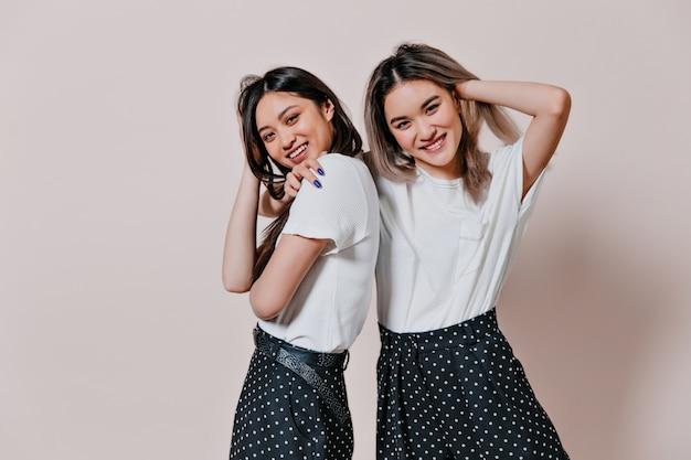 Belles sœurs en jupes à pois rient sur un mur beige