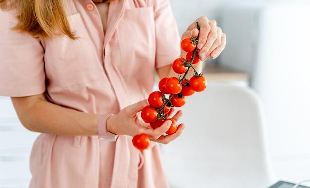 Belles tomates rouges sur une branche en mains.