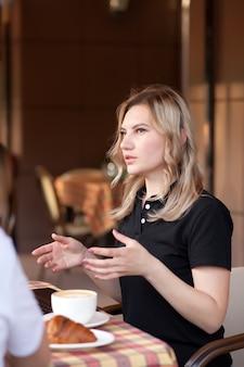 Belles travailleuses ou étudiantes utilisant un ordinateur portable au café et parlant