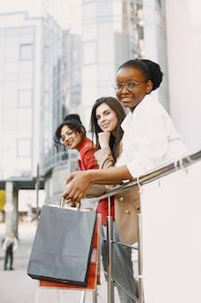 Belles trois jeunes femmes avec des sacs-cadeaux se promènent dans la ville. les femmes après le shopping s'amusent.