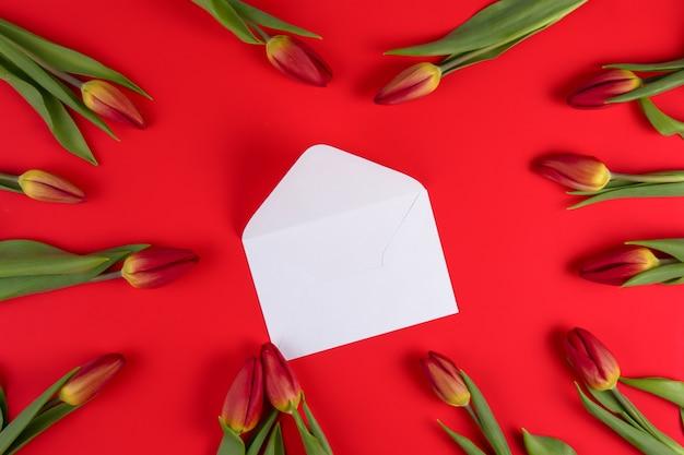 Belles tulipes autour d'une enveloppe ouverte blanche sur fond rouge