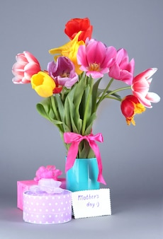 Belles tulipes en bouquet avec cadeaux et note sur gris