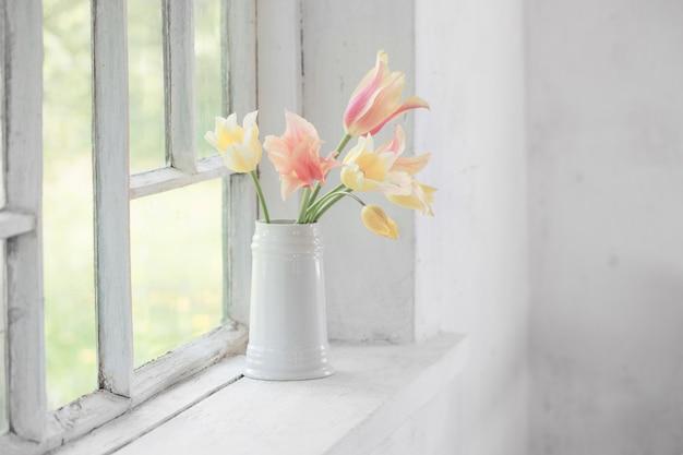 Belles tulipes dans un vase sur rebord de fenêtre blanc