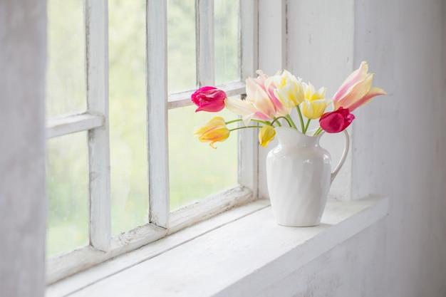 Belles tulipes dans un vase sur le rebord de la fenêtre blanche