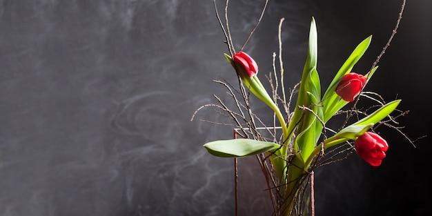 Belles tulipes fleurissent de couleur rouge dans un vase en verre sur fond noir. carte de voeux saint valentin ou fête des mères. copiez l'espace pour le texte. bannière