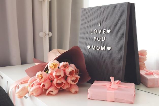Belles tulipes avec la lettre i love mom sur le panneau aux lettres. fond rose, cadre, bordure. belle carte de voeux avec des tulipes pour les concepts de fête des mères, de mariage ou d'événement heureux.