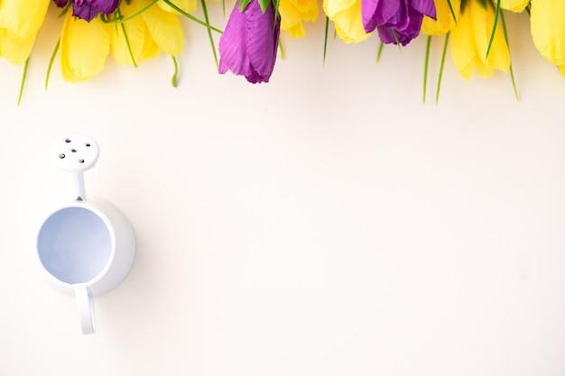 Belles tulipes lumineuses et arrosoirs comme concept de soin des fleurs.