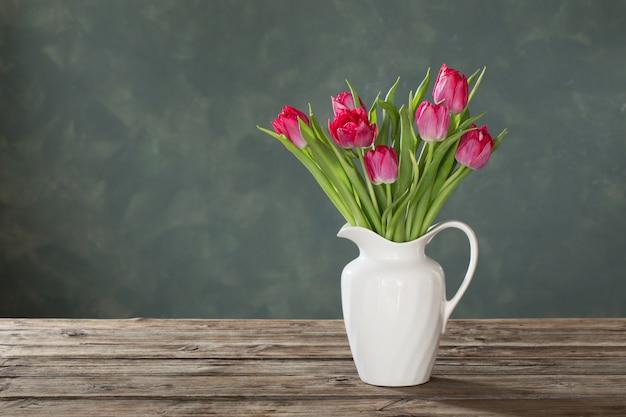 Belles tulipes en pot blanc sur fond sombre