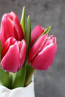 Belles tulipes roses dans un vase blanc sur fond en bois