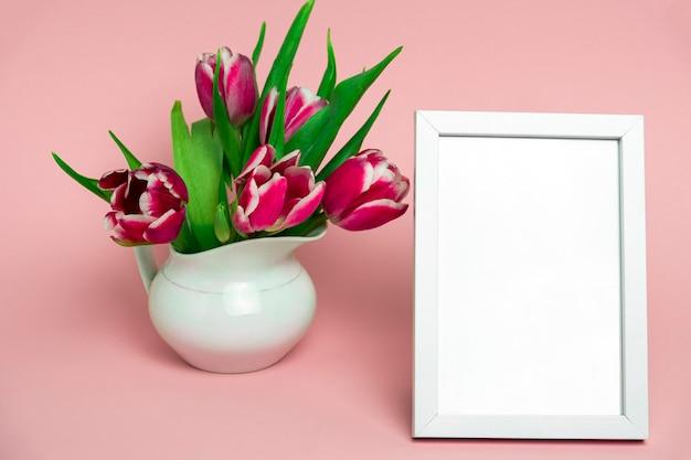 Belles tulipes roses fraîches dans un pot en porcelaine blanche et en bois blanc