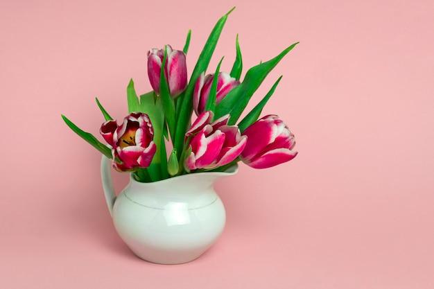 Belles tulipes roses fraîches dans un pot en porcelaine blanche sur un rose délicat