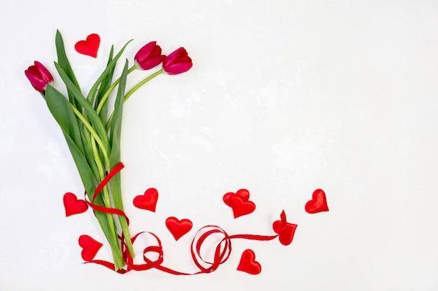 Belles tulipes rouges et coeurs de satin sur un fond texturé blanc avec espace copie