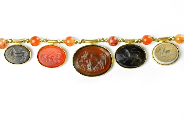 Belles variétés d'anciennes intailles pyu montées dans des pendentifs en or modernes enfilés sur d'anciennes petites perles d'or séparées par des perles de cornaline rondes sur fond blanc, myanmar
