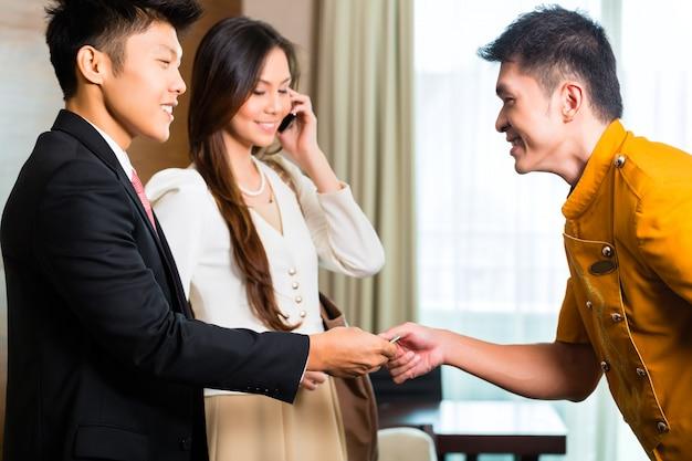 Bellier ou concierge asiatique chinois recevant un pourboire