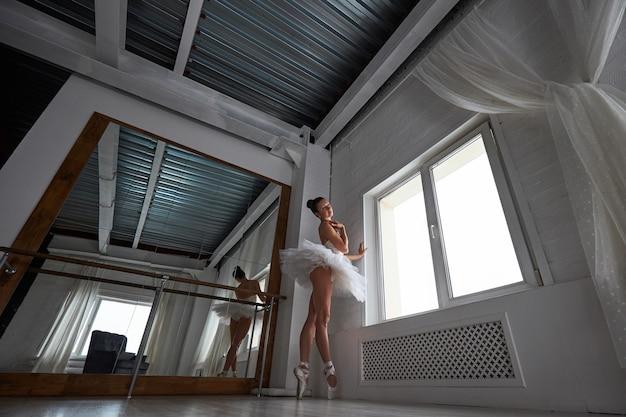 De belove vue de la belle ballerine debout à côté de la fenêtre en studio de ballet. copyspace