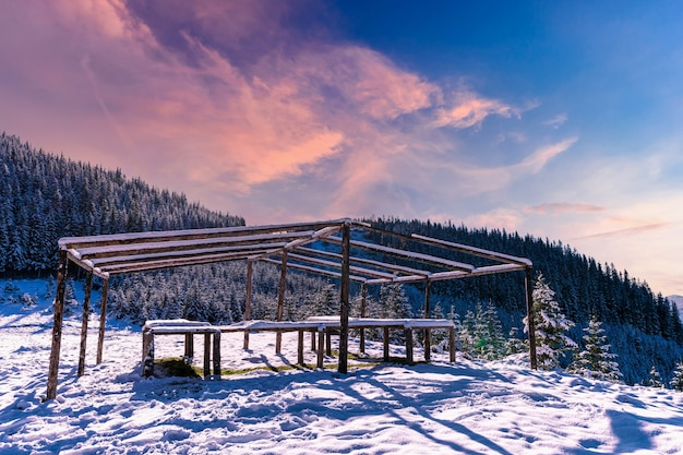 Le belvédère au sommet de la montagne se dresse dans une prairie enneigée, baignée par la lumière du soleil froid et éclatant