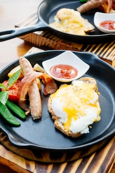 Bénédicte aux œufs, bacon à la saucisse et sauce tomate