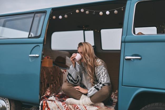 Bénéficiant d'une boisson chaude. jolie jeune femme buvant dans la tasse alors qu'elle était assise à l'intérieur de la mini-fourgonnette bleue de style rétro