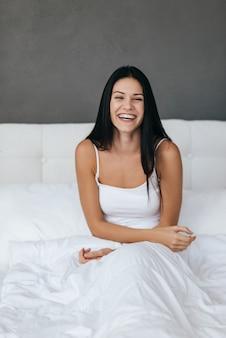 Bénéficiant d'un bonjour. belle jeune femme souriante au réveil le matin