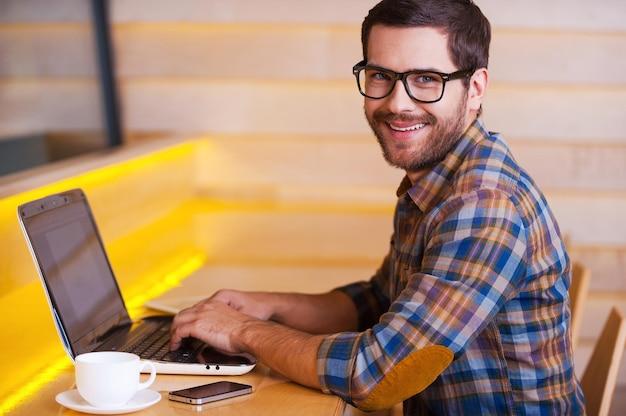 Bénéficiant d'une connexion wi-fi gratuite dans le café. beau jeune homme travaillant sur ordinateur portable et souriant assis dans un café