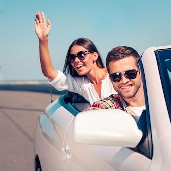 Bénéficiant d'un voyage en voiture. heureux jeune couple profitant d'un voyage sur la route dans leur cabriolet blanc