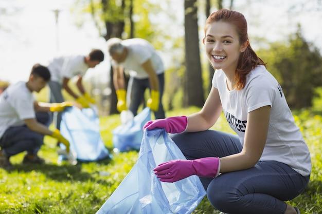 Bénévolat dans le parc. joyeuse bénévole souriante en ramassant des ordures