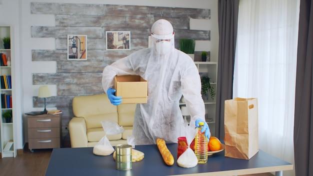 Bénévole en combinaison de protection contre les matières dangereuses tenant une boîte tout en y mettant de la nourriture.