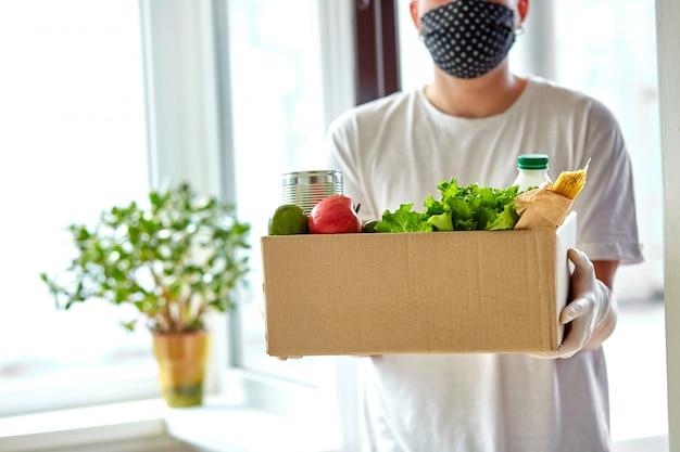 Bénévole dans la boîte de dons de masque médical de protection et de livraison de gants à la maison
