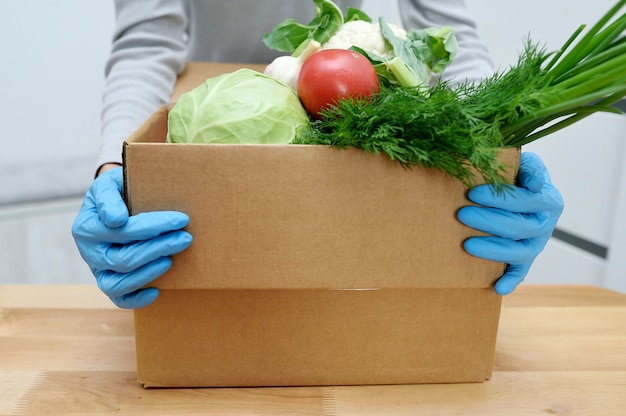 Une bénévole dans des gants détient des légumes dans une boîte de dons de nourriture pour aider les pauvres. boîte de donat avec des denrées alimentaires