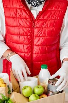 Bénévole dans le masque médical de protection et des gants mettant de la nourriture dans une boîte de dons