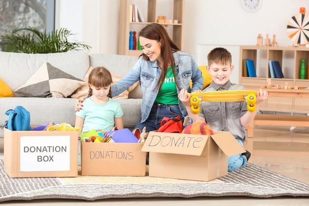 Bénévole avec des dons et des enfants à la maison des orphelins