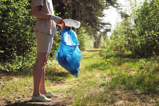 Un bénévole et éco-activiste ramasse les ordures dans des sacs, en forêt, gros plan. recyclage des déchets plastiques, protection de l'environnement. protéger la planète des débris. notion d'écologie.