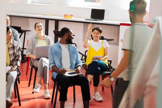Bénévole. étudiant assez gai levant la main et le séminaire et les camarades de classe souriant et la regardant