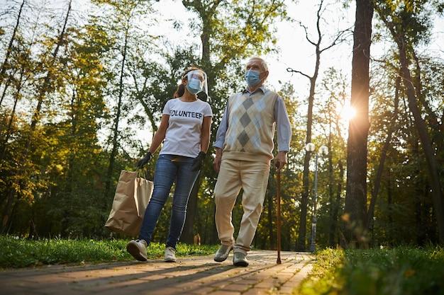 Bénévole femme parlant avec un homme âgé dans le parc de la ville