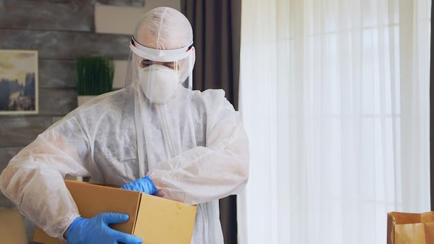 Bénévole mettant de la nourriture dans une boîte portant une combinaison de protection contre les matières dangereuses pour un don.