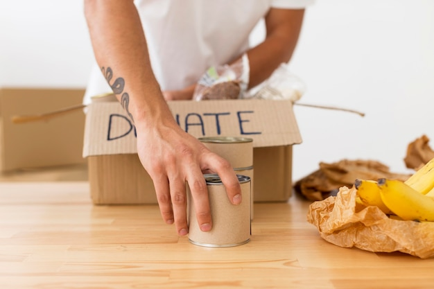 Bénévole plaçant des boîtes avec de la nourriture dans des boîtes close-up