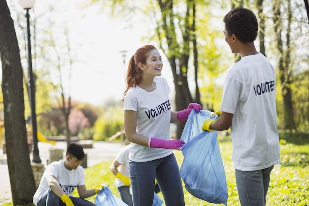 Bénévole pour le pays. joyeux deux bénévoles tenant un sac à ordures et se regardant
