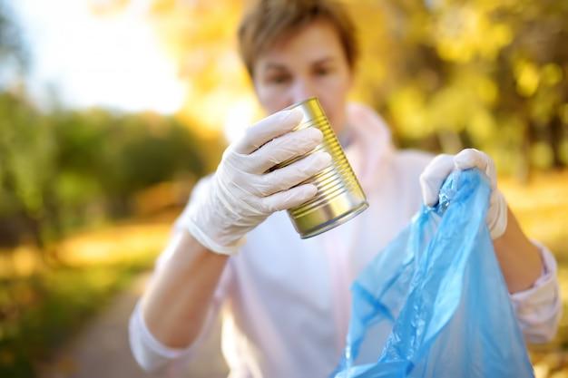 Bénévole ramassant les déchets et les mettant dans un sac poubelle biodégradable à l'extérieur.