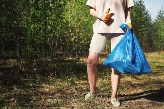 Un bénévole ramasse des bouteilles en plastique dans la forêt. la fille tient un sac d'ordures dans ses mains et montre un geste de la main : super, classe. appel de concept pour protéger l'environnement, la planète.