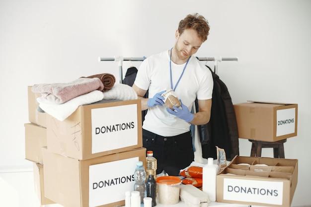 Le bénévole recueille des choses à partir de dons. guy emballe des boîtes avec des choses. l'homme compare la dotation.