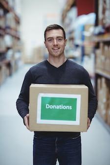 Bénévole souriant à la caméra tenant une boîte de dons dans un entrepôt