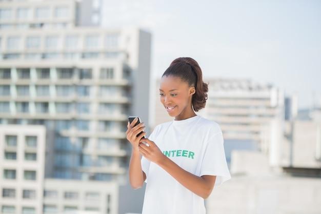 Bénévole souriant tenant son téléphone portable