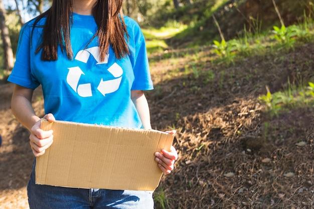 Bénévole tenant en carton dans la forêt