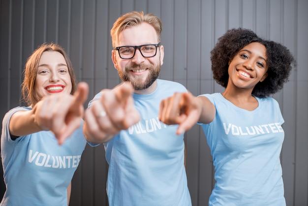 Des bénévoles heureux en t-shirts bleus pointant du doigt la caméra debout à l'intérieur
