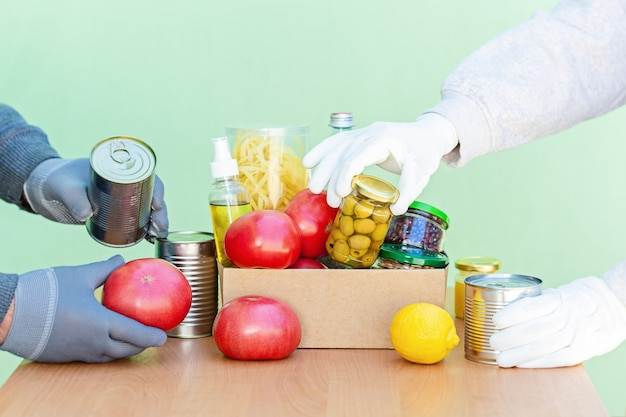 Les bénévoles remplissent une boîte en carton avec des produits pour soutenir les personnes dans le besoin