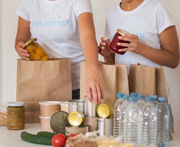 Bénévoles avec des sacs et de l'eau pour un don