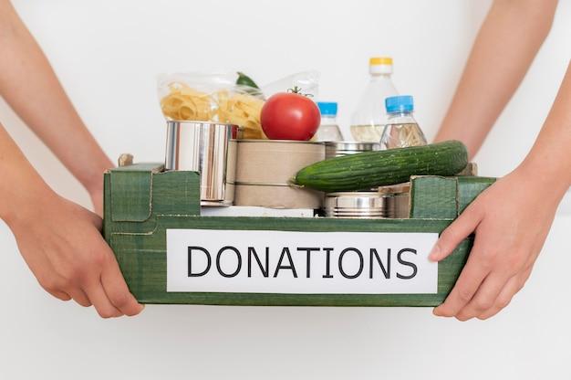 Bénévoles tenant une boîte remplie de nourriture pour le don