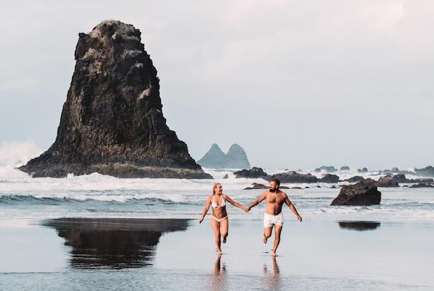 Benijo, tenerife, espagne : plage de sable naturel. endroit populaire pour la population locale et les touristes. des roches volcaniques jaillissent de l'eau turquoise et des vagues douces et douces lavent le rivage sablonneux.