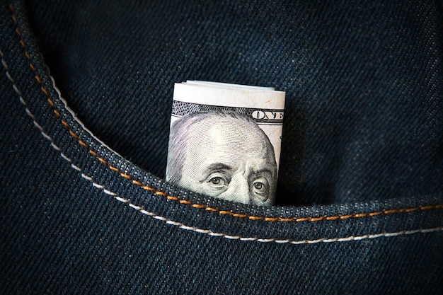 Benjamin franklin jetant un coup d'œil hors de la poche. cent dollars en denim de poche. billet américain en jeans. argent de poche. dépenses de poche