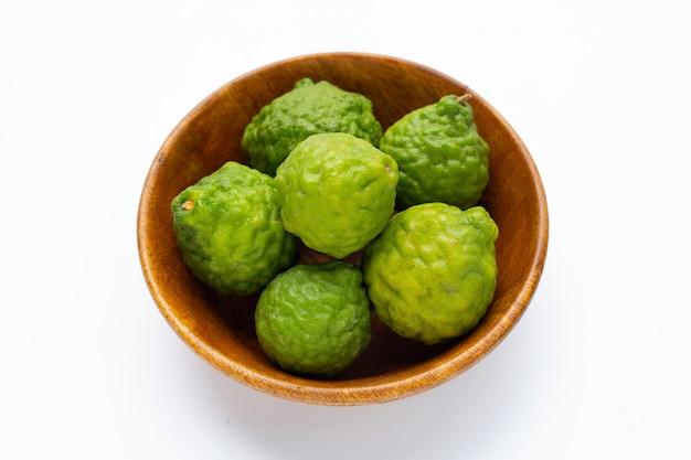 Bergamote kaffir lime fruits frais dans un bol en bois sur fond blanc.